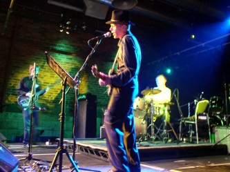 Jandek in a black stetson plays guitar flanked by a drummer and a bassist