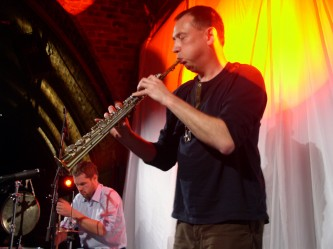 John Butcher and Ingar Zach performing on stage with saxophone and drums