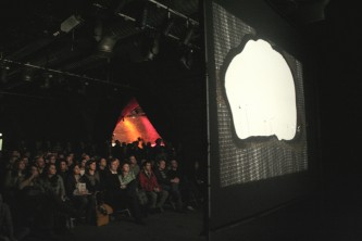 A large screen shows dissolving nylon before a large seated crowd
