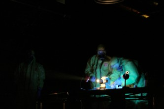 Two figures in chemical suits and masks perform a task