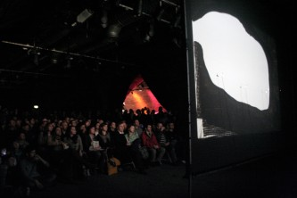 A large screen shows a blob of dissolving nylon before a large seated crowd