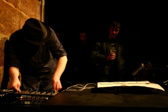 Ben Drew looks down at a table whilst performing in a dark space