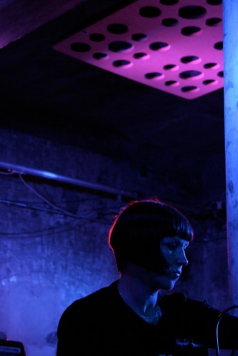 Karen Constance in profile, her bob highlit with red light