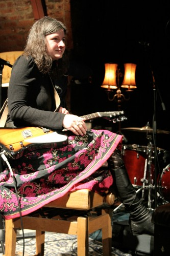 Erica Elder sits with a guitar on her lap smiling in a floral skirt