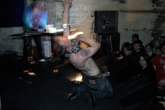 A bare chested man with a bandana of their face screams whilst moving a torch