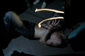 A bare chested man with a bandana of their face writhes on a floor with a torch