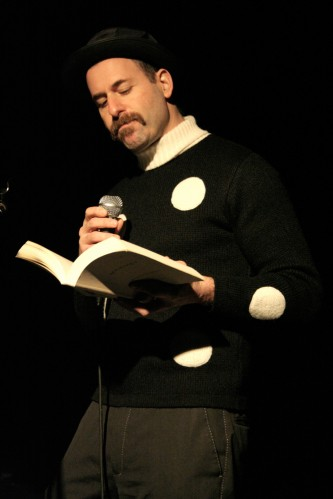 Kenny Goldsmith Frowns into a microphone wearing a white spotted jumper