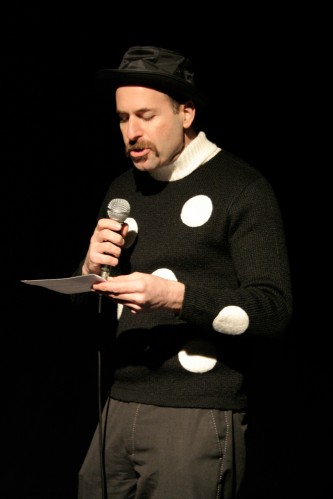Kenny Goldsmith speaks into a microphone wearing a white spotted jumper