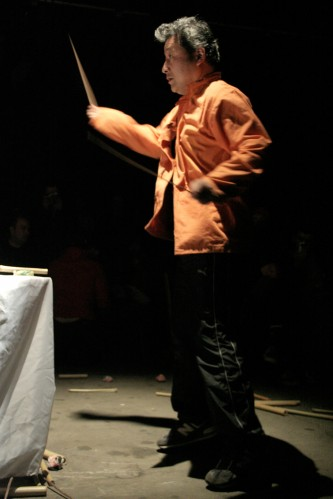 Masami Tada in an orange top moves bamboo switches through the air