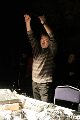 Kei Shii plays a wire in the air, hand raised