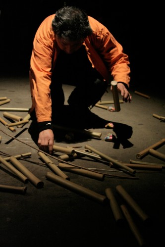 Masami Tada in an orange drops bamboo sticks onto others on the floor