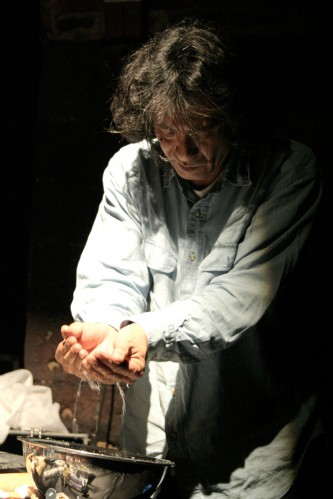 Kazuo Imai holds water in his hands above a metal bowl
