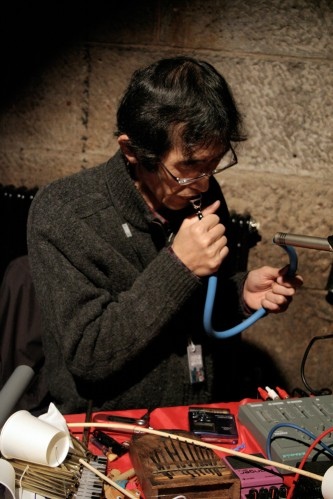 Tomonao Koshikawa plays a blue pipe a table of objects in front
