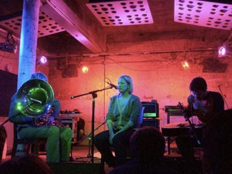Robin, Aileen and Neil performing in pink lit club space