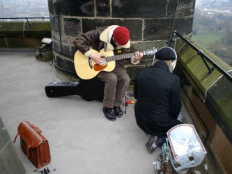 a guitarist and singer perform at the top of the Glasgow University Bell Tower