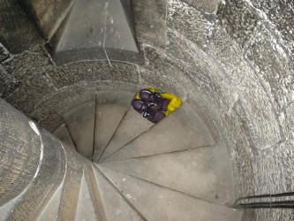A pair of shoes on a step within a spiral staircase, viewed from above
