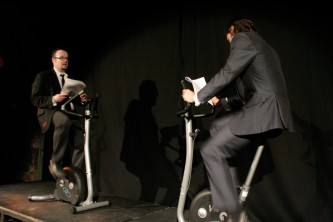 Two men wearing suits reading on exercise bikes