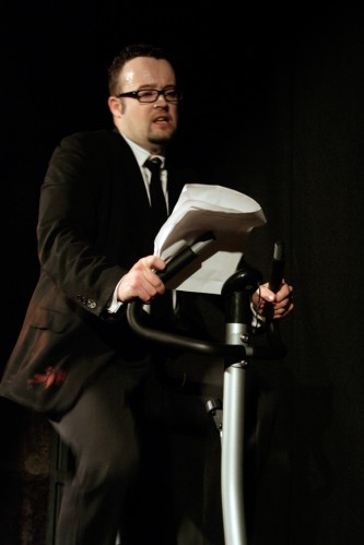 A man reads from papers on an exercise bike, a red paint stain on his suit