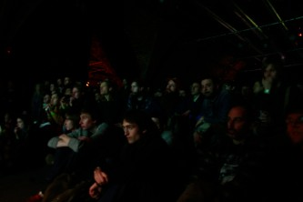 An audience watch the performance in a dark space