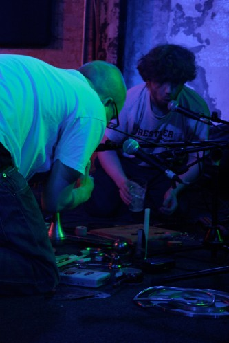 Two members of Usurper kneel on the floor whilst they are performing