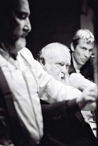 Hermann Nitsch plays organ flanked by two assistants
