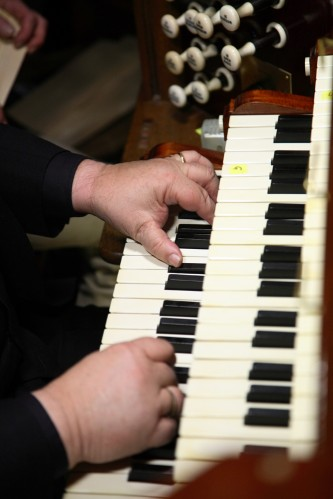 Two hands plays a two tiered organ keyboard