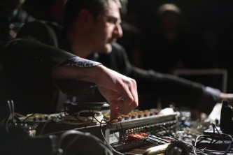 A blurred face and a clear hand suspended above a mixing board
