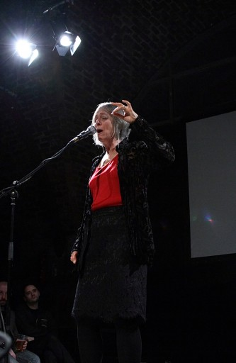 Joan La Barbara in red top holds her hand up as she sings lit by stage lights