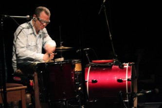 Fritz Welch plays a red drum kit whilst grimacing