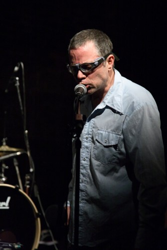 Fritz Welch in goggle spectacles and a blue shirt stands as he sings into a mic
