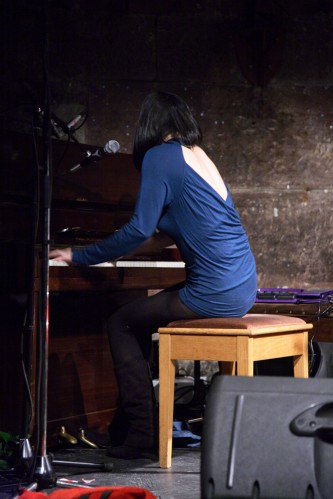 Mico in a blue backless dress sits on a stool as she plays the pianos