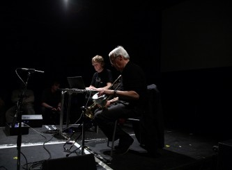 Two men play instruments sat on a dark stage