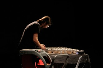 Nikos Veliotis in safety goggles fills jars with chipped wood