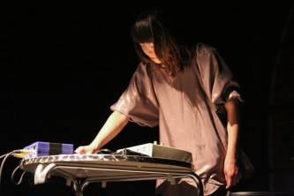 A performer leans over a mixer, they are lit but the space is dark