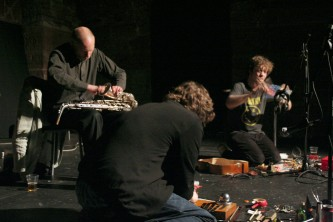Three performers all heads down as they concentrate on performing