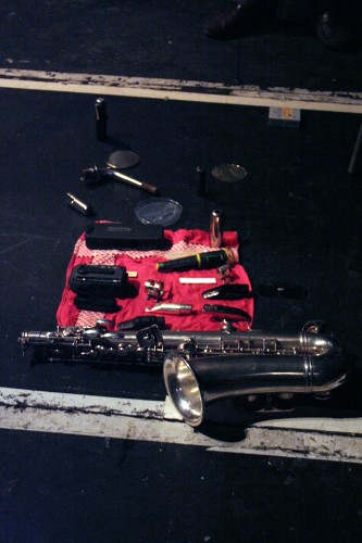 A red hankerchief on the floor has several musical objects and a saxophone on it