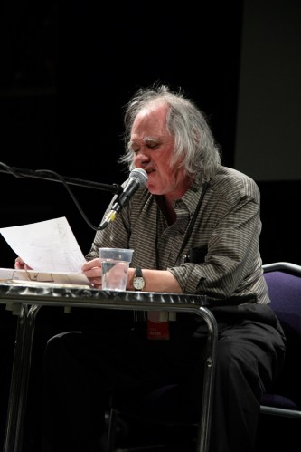 Steve McCaffery sits at a round table and reads from a paper into a microphone