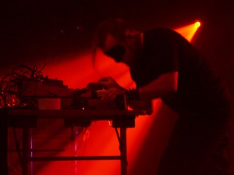 Masked man evokes Iron Maiden childhood using a mixer and red light