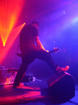 A musician plays a low slung flying v guitar with a foot on a monitor