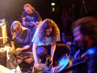 Four performers work with instruments on a stage floor
