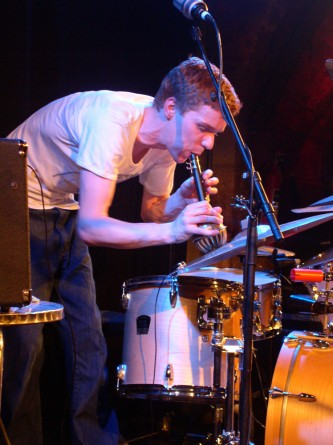 a drummer blows a wind instrument into a metal bowl