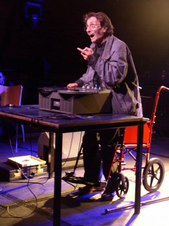 a man stands above a wheel chair gesticulating with his hands