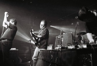 Three performers on stage in the arches with equipment