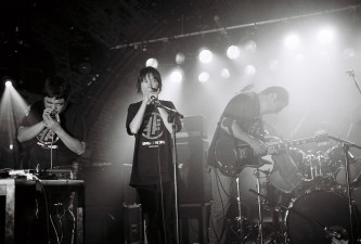 Hijokaidan on stage performing with intensity and strong lighting