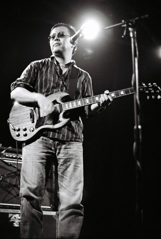 A man playing the guitar lit from behind