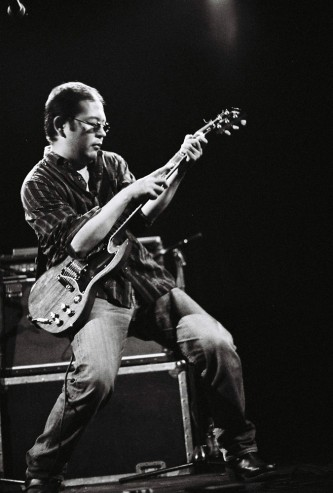 A man holds a rock star pose while eliciting guitar feedback