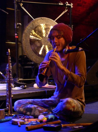 a man blows a wind instrument in front of a gong