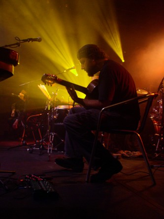 Richard Bishop playing a guitar seated in yellow light