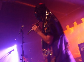 A masked performer blows a wind instrument in pink light