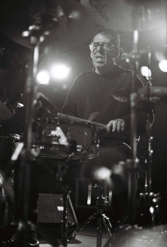 a drummer as though in mist or fog, sticks in hands